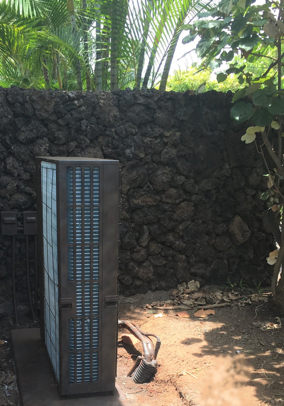 Thompson Art Studios faux painted air conditioner unit to blend into the surrounding lava rock wall.