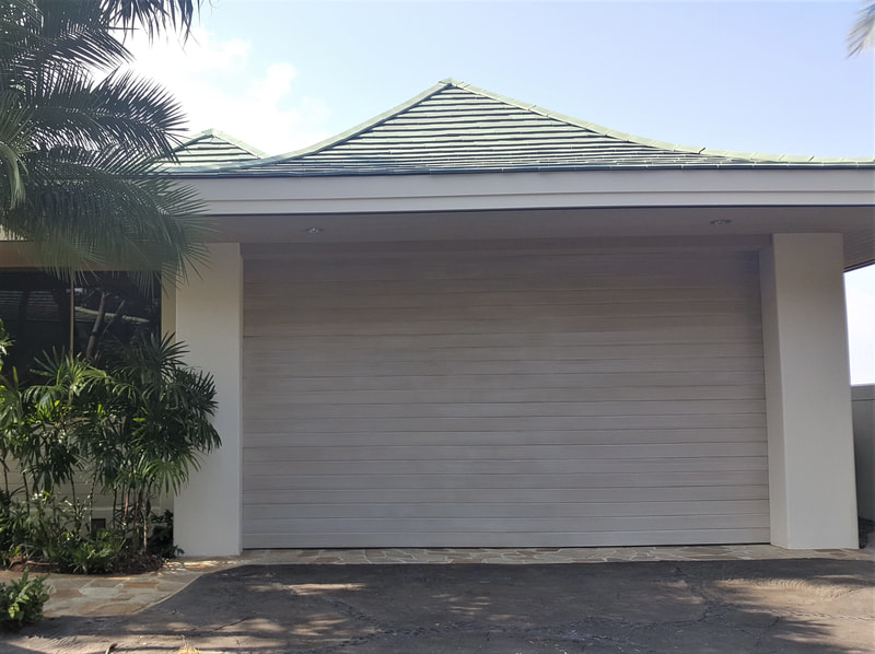 Thompson Art Studios' rehabilitated the worn wood plank garage door on this Mauna Kea Fairways residence with a pickled paint treatment.